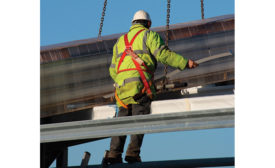 A Construction Worker Protected by a Guardrail and a Fall Arrest System