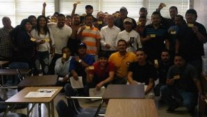 Employees proudly showing their OSHA 10 cards with OSHA trainer Mark A. Hernandez (in orange shirt).